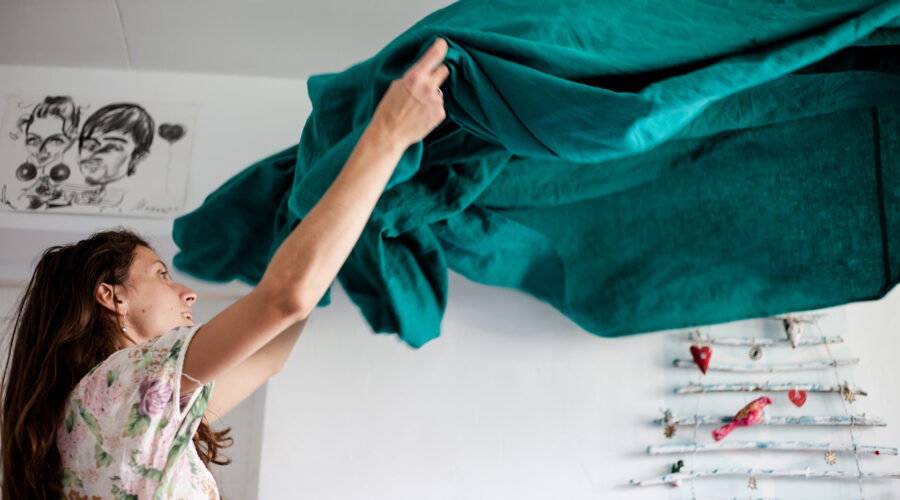 woman shakes out green sheets