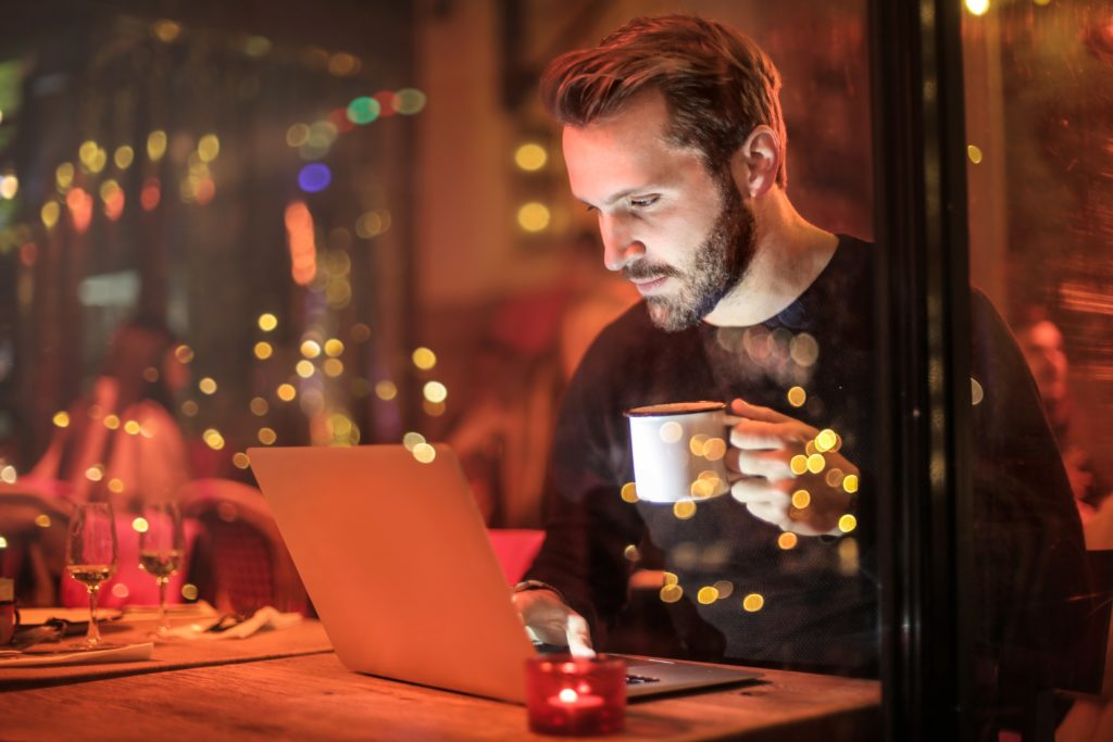 Man sitting in a restaurant drinking coffee and using a laptop
