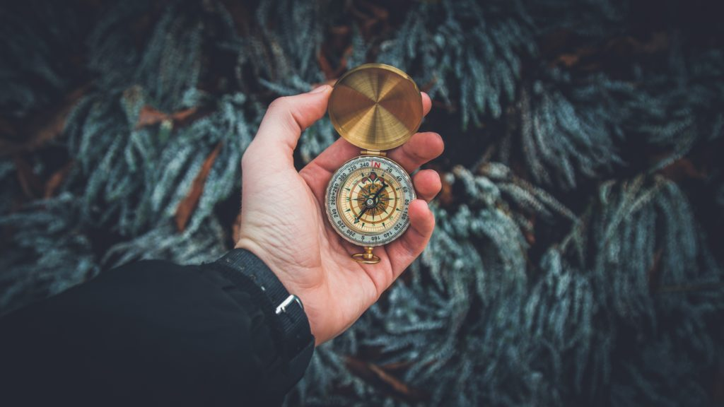 Man holding a gold compass in front of greenery