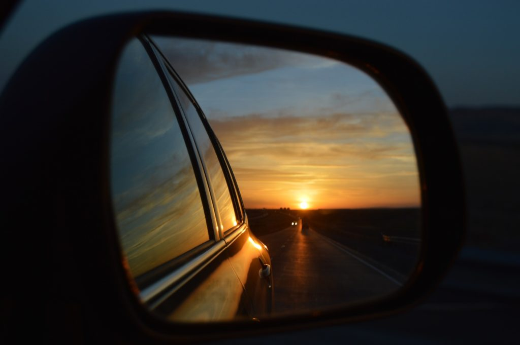 reflection of a sunset in a rear view car mirror