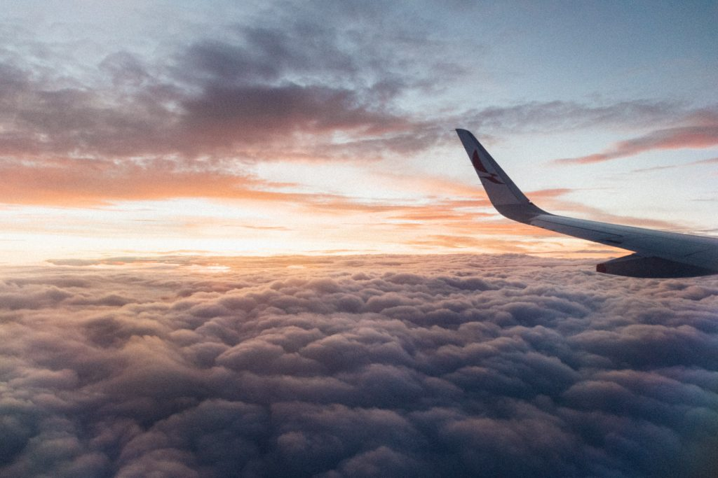 Airplane flying above the clouds at sunset